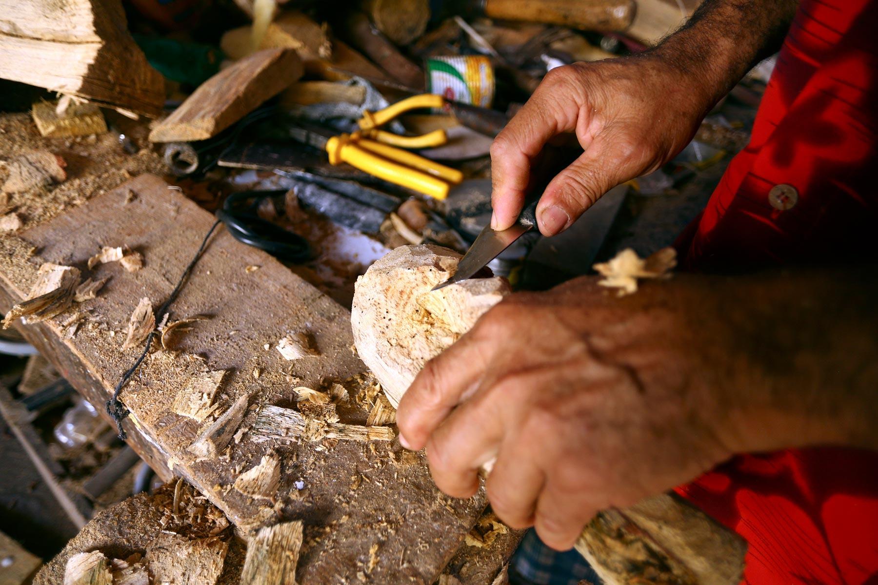 Miro esculpe a cabeça de um Simão, figura do mamulengo que é conhecida por começar   a brincadeira popular