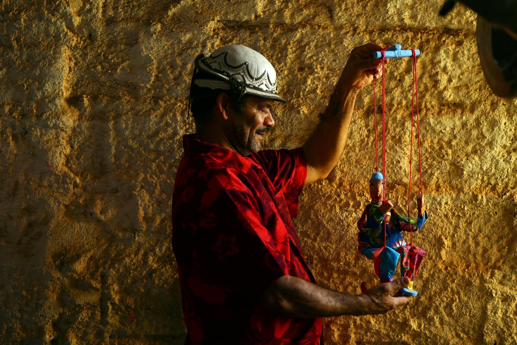 O artista popular Miro dos Bonecos examina uma de suas marionetes, feita com chita   e madeira de mulungu