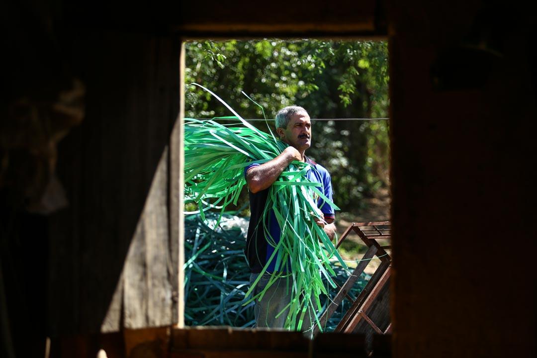 Timóteo Guimarães, conhecido como Zelão, leva fitas e lacres de plástico para desinfetar em casa, na Vila Santa Luzia, distrito de Belo Jardim - Foto: Peu Ricardo