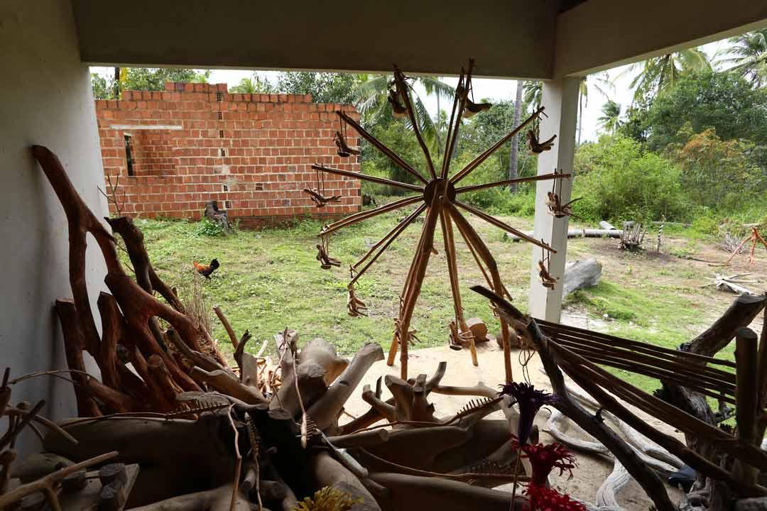 Raízes e peças já esculpidas se espalham no terraço da casa de Mestre Abias, que criou até uma roda-gigante de 1,80m para a Fenearte; ao fundo, paredes de um ateliê em construção - Foto: Peu Ricardo