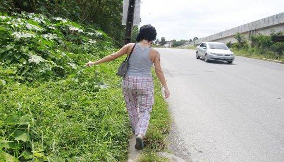 Pedestre se equilibra no meio fio por falta de espaço
